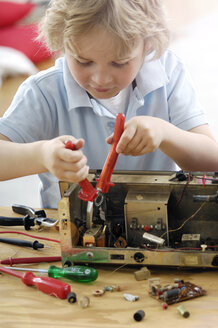 Little boy disassembling an old radio - GUFF000225