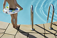 Back view of little boy with floating tire standing at pool edge - GUFF000228