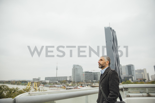 Austria, Vienna, businessman standing on Reichsbruecke in front of DC Towers - AIF000215 - AustrianImages/Westend61