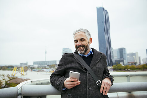 Austria, Vienna, smiling businessman standing on Reichsbruecke looking at his smartphone - AIF000218