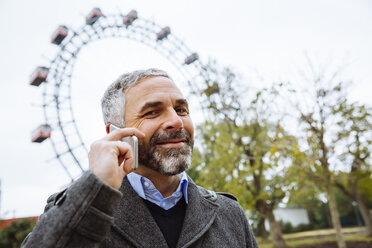 Austria, Vienna, portrait of smiling businessman telephoning with smartphone at Prater - AIF000226