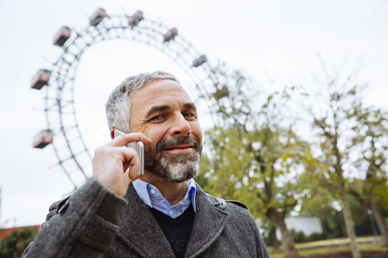Austria, Vienna, portrait of smiling businessman telephoning with smartphone at Prater - AIF000226 - AustrianImages/Westend61