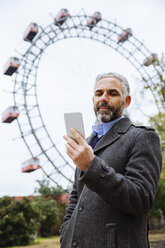 Austria, Vienna, portrait of businessman looking at his smartphone at Prater - AIF000229