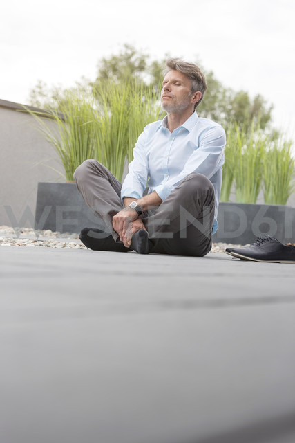 Mature man taking a break on rooftop terrace - LOF003702