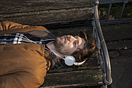 Portrait of young man lying on a bench hearing music with headphones - FMKF002239