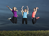 Three young women jumping together in the air - STSF000992