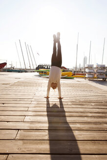 Spain, Barcelona, girl doing a handstand on jetty - VABF000036