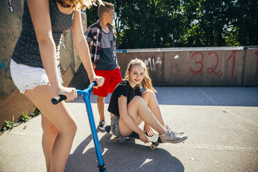 Three teenage friends with scooter and skateboard - AIF000258
