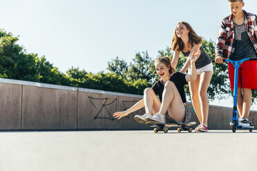 Three playful teenage friends with scooter and skateboard - AIF000261