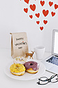 Still life with laptop, donuts, Valentine's day present and hearts on wall - EBSF001231