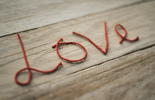 The word 'Love' formed of red threads on wood - JPF000100