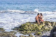Happy couple in love sitting on rock in the sea - SIPF000016
