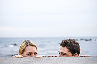 Playful young couple looking at each other behind a wall - SIPF000028