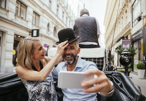 Austria, Vienna, couple having fun on sightseeing tour in a fiaker - AIF000279