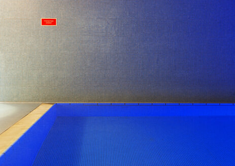 Empty indoor swimming pool with sign at the wall - WWF003911