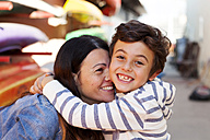 Spain, Barcelona, portrait of happy little boy hugging his mother - VABF000039