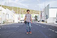 Spain, Tenerife, portrait of boy standing on a road with his skateboard - SIPF000040