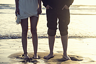 Spain, Cadiz, legs of young couple standing barefoot atseafront - KIJF000109