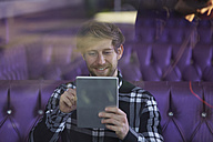 Young man sitting in a lounge bar using digital tablet - FMKF002241
