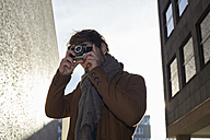 Young man taking a picture with vintage camera - FMKF002253