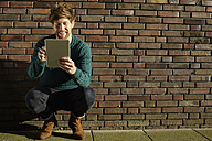 Young man crouching in front of a brick wall using digital tablet - FMKF002256