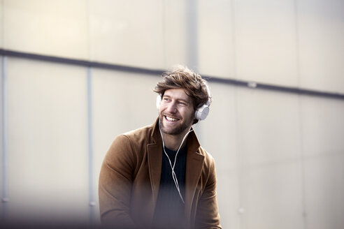 Smiling young man listening music with headphones at backlight - FMKF002259