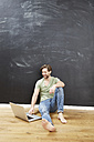 Portrait of smiling young man sitting  in front of chalkboard on the floor using laptop - FMKF002265
