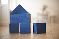 Blue wooden building bricks shaping a house - FMKF002271