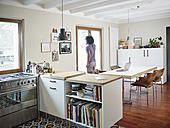 Young man looking out of window in open plan kitchen - RHF001225