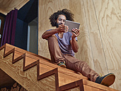 Young man on wooden stairs looking at digital tablet - RHF001234