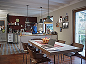 Laptop on dining table in open plan kitchen with man in background - RHF001246