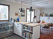 Woman using laptop in open plan kitchen - RHF001255