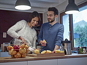 Couple in kitchen slicing oranges for freshly squeezed orange juice - RHF001264
