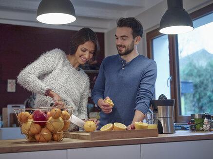 Couple in kitchen slicing oranges for freshly squeezed orange juice - RHF001264