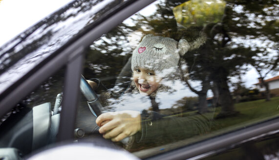 Portrait of happy little girl sitting on her mother's lap while driving car - MGOF001247