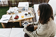 Pensive woman sitting on balcony with cup of tea - JRFF000287