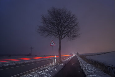 Germany, Lower Saxony, dribing cars on road, fog in the evening, long exposure - PVCF000740