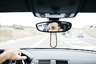 Young man driving a car, close up of rear mirror - JRFF000328