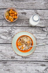 Bowl with cereals and physalis, milk bottle on wood - LVF004394