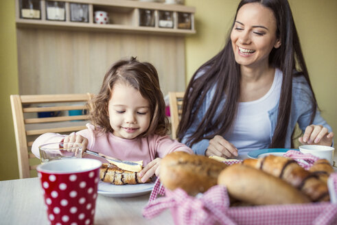 Portrait of mother and her little daughter at breakfast table - HAPF000110