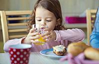 Portrait of little girl drinking glass of orange juice at breakfast table - HAPF000113
