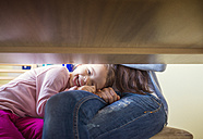 Portrait of little girl with head in her mother's lap - HAPF000116