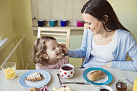 Portrait of mother and her little daughter having fun at breakfast table - HAPF000119