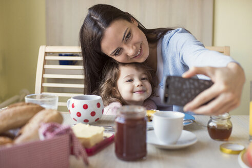 Portrait of mother and her little daughter taking a selfie at breakfast table - HAPF000125