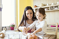 Portrait of little girl and her mother rolling out dough together on kitchen table - HAPF000140