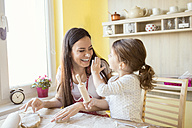 Mother and her little daughter having fun together while they are baking - HAPF000143