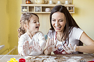 Portrait of laughing mother and her little daughter baking together - HAPF000155