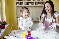 Portrait of laughing mother and her little daughter baking together - HAPF000158