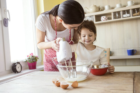Portrait of smiling little girl and her mother baking together - HAPF000161
