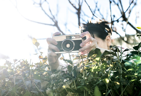 Woman shooting pictures over a hedge with an old camera - DEGF000604